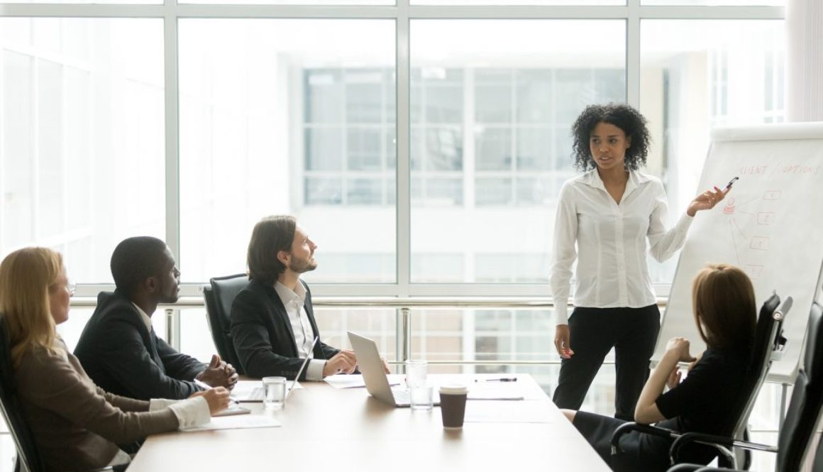 African American Businesswoman Giving Presentation To Executive